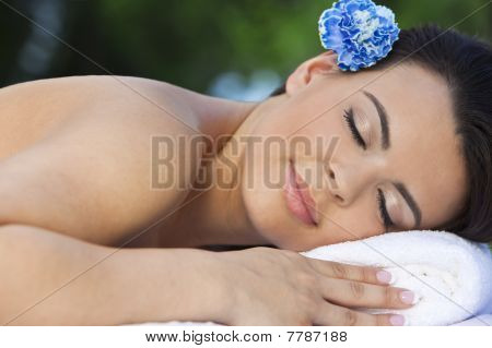 Beautiful Brunette Woman Relaxing At Health Spa With Blue Flower
