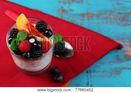 Healthy breakfast - yogurt with  fresh fruit, berries and muesli served in glass, on color wooden background