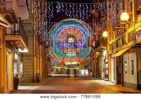 ALBA, ITALY - jANUARY 03, 2013: Decorated street and illuminated observation wheel in old town of Alba as part of traditional Christmas and New Year celebrations.