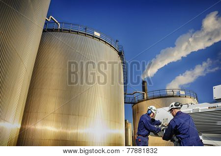 oil workers with pumps and large storage tanks