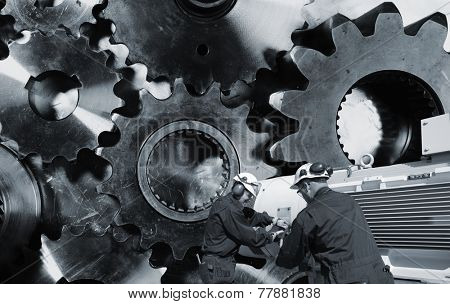 mechanics, engineers with large cogwheels and gear machinery