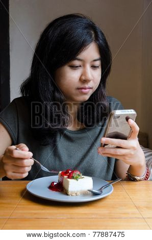 Young Asian Woman Chating Mobile Phone With A Cake