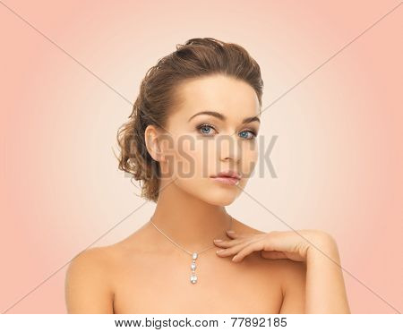 beauty, people and jewelry concept - woman wearing shiny diamond pendant over pink background