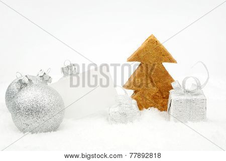 Silver Christmas Decoration On Snow With Wishes Card And Cookie