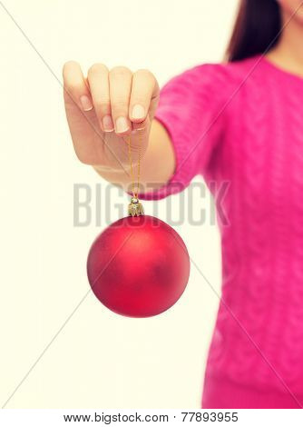 christmas, holidays and people concept - close up of smiling woman in pink sweater holding christmas ball