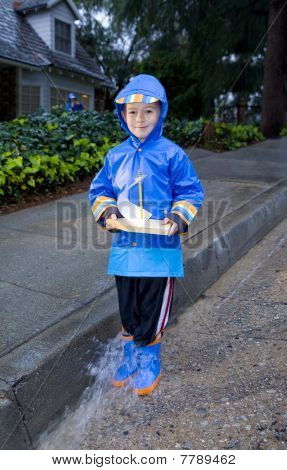 Young Boy Playing With Toy Boat In The Rain 4