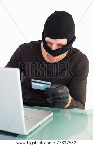 Burglar shopping online with laptop on white background