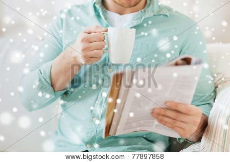 rest, news, drinks and people concept - close up of man reading magazine and drinking from cup sitting on couch at home