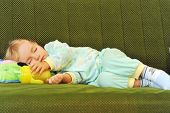 picture of arms race  - little girl sleeping on the green couch - JPG