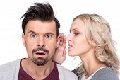 stock photo of ear  - Amazed man is listening gossip in the ear from woman on the white background - JPG