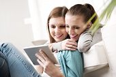 foto of lesbian  - Happy lesbian couple spending time together with tablet on sofa at home. ** Note: Shallow depth of field - JPG