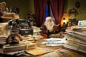 pic of letters to santa claus  - Messy Santa Claus desk with letters and vintage phone he is sitting on the background and reading a book - JPG