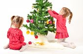 picture of twin baby girls  - Twin Girls are decorating Christmass Tree with home made Ornaments isolated on white Background - JPG