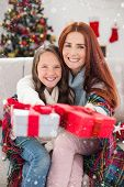 picture of blanket snow  - Festive mother and daughter wrapped in blanket with gifts against snow falling - JPG