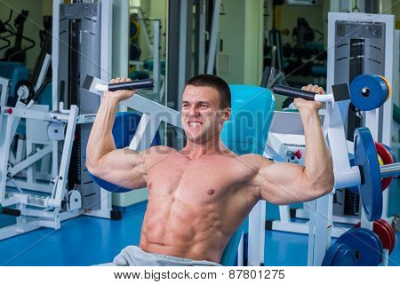 Fit man exercising at the gym on a machine.Man at the gym. Man makes exercises. Sport, power, dumbbe