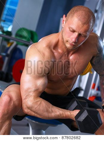 Strong man, bodybuilder exercising with dumbbells in a gym
