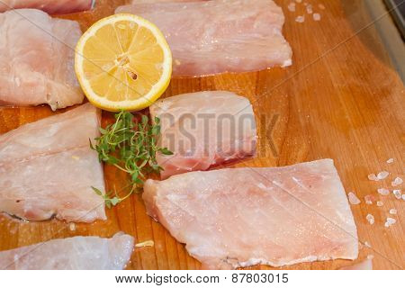 fresh fish on wooden cutting board ready for cooking