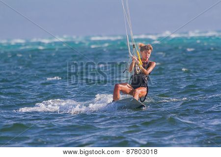 A young woman kite-surfer rides in blue sea