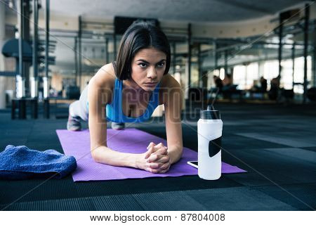 Beautiful fit woman working out on yoga mat at gym