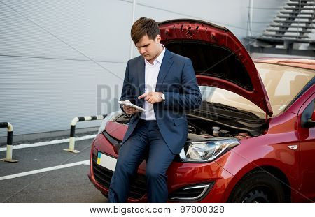 Businessman Sitting On Hood Of Broken Car And Searching How To Fix It