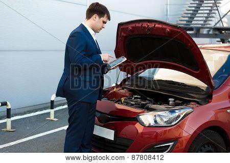 Sales Manager Making Photo Under Car Bonnet