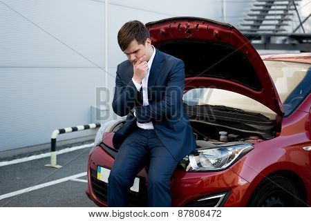 Man Sitting On Bonnet Upset Because Of Broken Car
