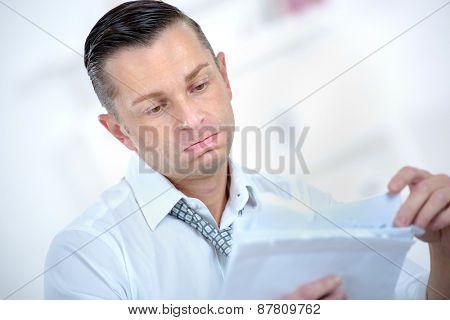 Depressed man looking at paperwork