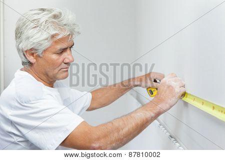 Mason measuring a white wall