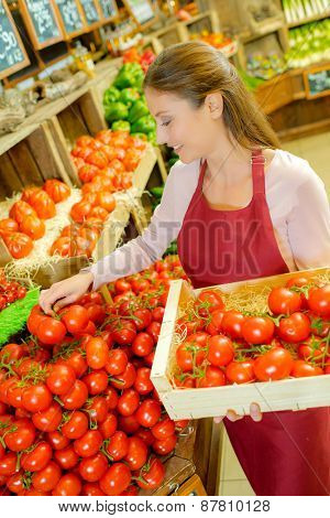 Woman stacking tomatoes