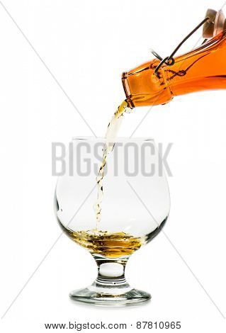 Pouring a glass of brandy from a bottle isolated on a white background