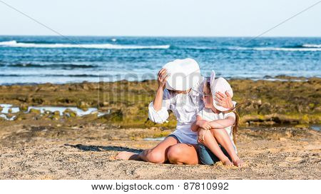 happy mother with daughter playing on the beach