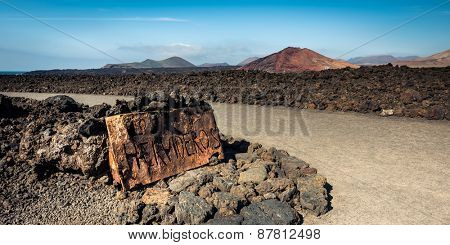 beautiful desert landscape with a metal sign Los Hervideros on Lanzarote island , Canary Islands