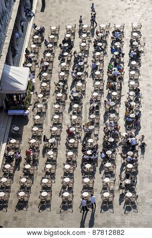 Tourists On San Marco Square Rest In An Alfresco Cafe