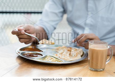 Man having Indian meal at cafeteria.