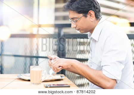 Asian Indian businessman eating roti at cafeteria.