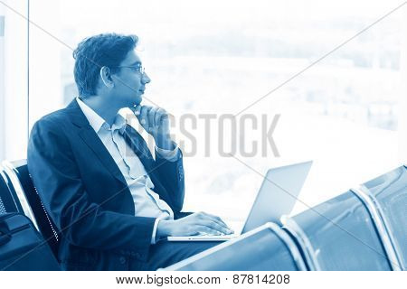 Asian Indian business man waiting his flight at airport, thoughtful and sitting on chair, blue tone.