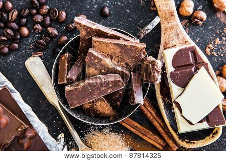 chocolate, cocoa beans and spices in the spoons on a dark table