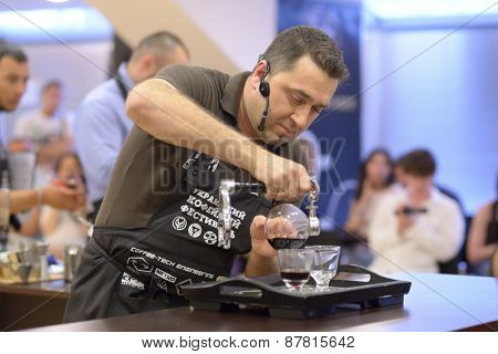 DNEPROPETROVSK, UKRAINE - JUNE 1, 2013: Barista Vitaly Panchenko makes the beverage during 5th Ukrainian Coffee In Good Spirits Championship in Dnepropetrovsk, Ukraine on June 1, 2013