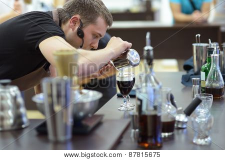 DNEPROPETROVSK, UKRAINE - JUNE 1, 2013: Barista Dmitry Shevchenko makes Irish coffee during 5th Ukrainian Coffee In Good Spirits Championship in Dnepropetrovsk, Ukraine on June 1, 2013