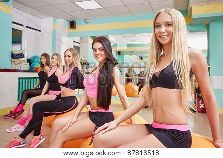 Beautiful athletic girls posing in fitness gym