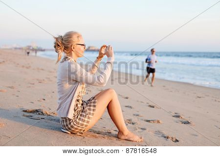 Barefoot smiling girl in glasses sitting on sand beach and taking pictures by smartphone in sunrise