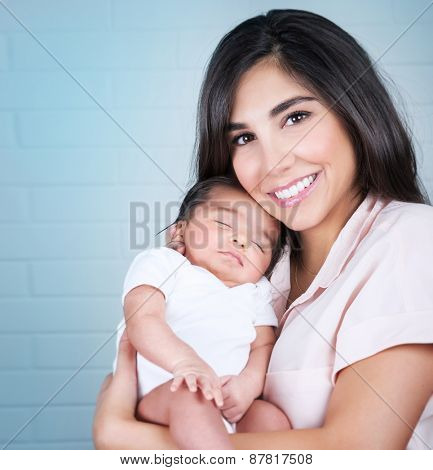 Portrait of happy smiling mother with cute sleeping baby on hands, spending time at home, loving family concept