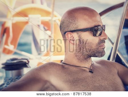 Closeup portrait of handsome shirtless man on sailboat, sexy sailor wearing sunglasses and enjoying sea trip, active lifestyle, summer travel and vacation concept