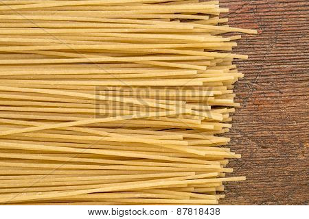 uncooked gluten free, brown rice pasta, spaghetti style on a rustic wood table
