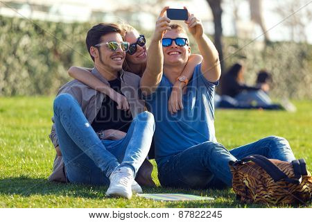 Group Of Students Taking Photos With A Smartphone In The Street.