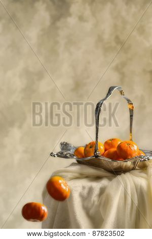Mandarin oranges falling from an antique silver fruit dish