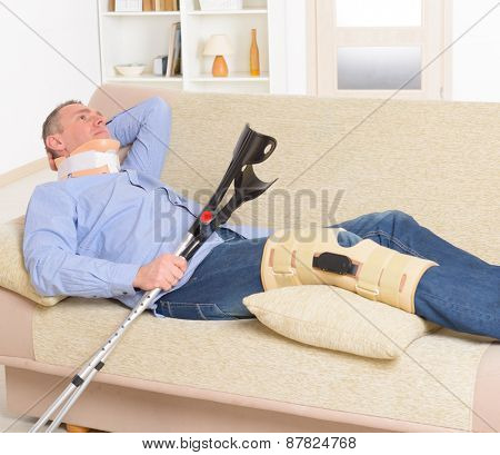 Man with leg in neck brace, knee cages and crutches for stabilization and support resting on a sofa