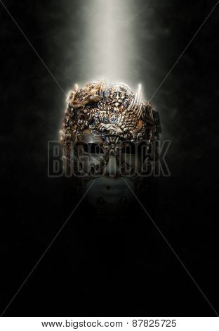 Ornate and Intricately Carved Mask Illuminated from Above by Bright Spotlight on Dark Background