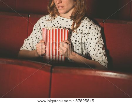 Young Woman Clutching Popocorn In Cinema