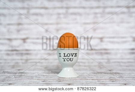 I Love You egg cup with a farm fresh brown boiled hens egg for a sentimental breakfast greeting on rustic grey wood background with copyspace